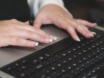 Mujer que pulsa en la computadora portátil Imagen de archivo libre de regalías