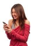 Mujer que pulsa y que envía SMS en el teléfono celular móvil Foto de archivo