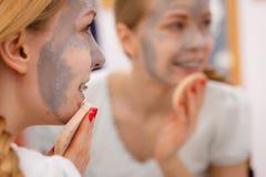 Mujer que quita la máscara facial del fango con la esponja Foto de archivo