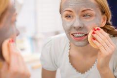 Mujer que quita la máscara facial del fango con la esponja Fotos de archivo