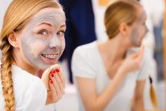 Mujer que quita la máscara facial del fango con la esponja Imágenes de archivo libres de regalías