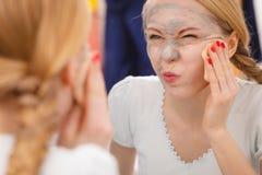 Mujer que quita la máscara facial del fango con la esponja Foto de archivo libre de regalías