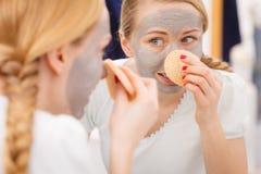 Mujer que quita la máscara facial del fango con la esponja Fotografía de archivo libre de regalías