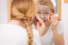 Mujer que quita la máscara facial del fango con la esponja Fotografía de archivo
