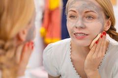 Mujer que quita la máscara facial del fango con la esponja Fotos de archivo libres de regalías