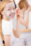 Mujer que quita la máscara facial del fango con la esponja Imagen de archivo libre de regalías
