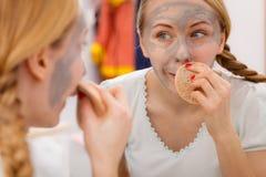 Mujer que quita la máscara facial del fango con la esponja Imagen de archivo