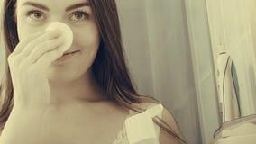 Mujer que quita maquillaje con el cojín de la esponja de algodón Imagenes de archivo