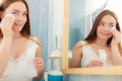 Mujer que quita maquillaje con el cojín de la esponja de algodón Imagen de archivo libre de regalías