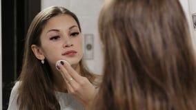 Mujer que quita maquillaje de su cara en cuarto de baño almacen de video