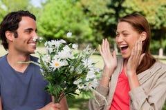 Mujer que ríe emocionado como ella le presenta con las flores Fotografía de archivo libre de regalías