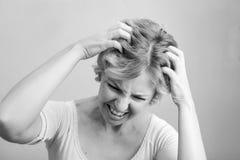 Mujer que rasguña su cabeza aislada en el fondo blanco truncamiento imagen de archivo