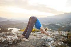 Mujer que realiza actitud hacia abajo de la yoga del perro al aire libre Imagenes de archivo
