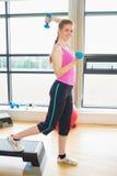 Mujer que realiza ejercicio de los aeróbicos del paso con pesas de gimnasia Fotos de archivo