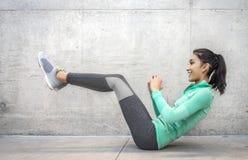 Mujer que realiza ejercicio del crujido de la base Foto de archivo