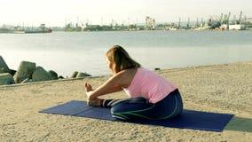 Mujer que realiza ejercicios de la yoga en la playa