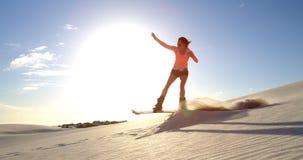Mujer que realiza un salto mientras que arena que sube a 4k metrajes