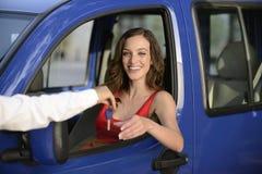 Mujer que recibe claves de su nuevo coche Foto de archivo libre de regalías
