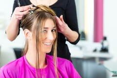 Mujer que recibe corte de pelo de estilista o de haird Imagen de archivo libre de regalías