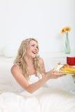 Mujer que recibe el desayuno en cama Imágenes de archivo libres de regalías