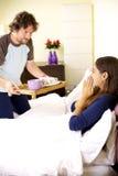 Mujer que recibe el desayuno en cama de marido Imagenes de archivo