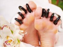 Mujer que recibe el masaje de piedra en pies. Foto de archivo