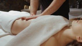 Mujer que recibe el masaje en el salón del balneario, mentira de relajación del estómago en procedimiento del rejuvenecimiento de almacen de video