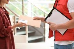 Mujer que recibe el sobre de mensajero del servicio de entrega imágenes de archivo libres de regalías