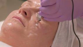 Mujer que recibe el tratamiento facial estimulante con el equipo microcurrent Plan del primer de electrodos en las manos de a almacen de video
