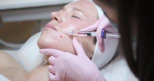 Mujer que recibe la inyección del botox en su mejilla metrajes