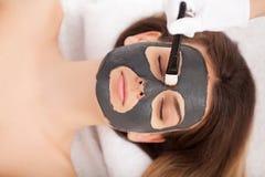 Mujer que recibe la máscara facial en el salón de belleza Fotos de archivo libres de regalías