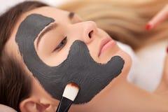 Mujer que recibe la máscara facial en el salón de belleza Imágenes de archivo libres de regalías