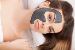 Mujer que recibe la máscara facial en el salón de belleza Imagen de archivo libre de regalías
