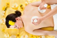 Mujer que recibe masaje con las bolas herbarias de la compresa en el balneario Fotografía de archivo