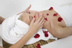 Mujer que recibe masaje de cara de las manos femeninas Fotos de archivo libres de regalías