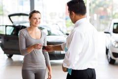 Mujer que recibe nueva llave del coche Foto de archivo libre de regalías