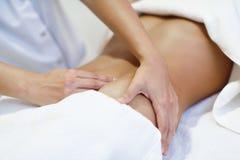 Mujer que recibe un masaje del vientre en el salón del balneario Imagen de archivo libre de regalías