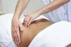 Mujer que recibe un masaje del vientre en el salón del balneario Imagen de archivo