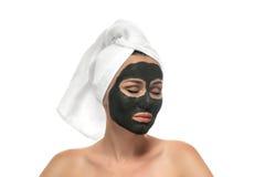 Mujer que recibe una máscara del fango en el fondo blanco. Foto de archivo libre de regalías