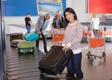 Mujer que recoge el equipaje en la banda transportadora en aeropuerto Imagenes de archivo