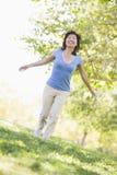 Mujer que recorre al aire libre sonriendo Fotografía de archivo
