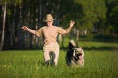 Mujer que recorre con el perro Foto de archivo libre de regalías