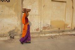 Mujer que recorre con una carga imagen de archivo libre de regalías