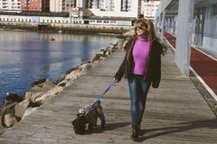 Mujer que recorre el perro Imagen de archivo