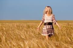Mujer que recorre en campo de trigo Imagen de archivo