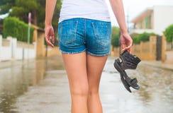Mujer que recorre en la lluvia Fotos de archivo