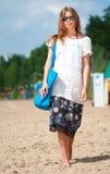 Mujer que recorre en la playa de la arena con el bolso Fotos de archivo libres de regalías