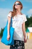 Mujer que recorre en la playa de la arena con el bolso Imagenes de archivo