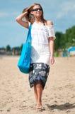 Mujer que recorre en la playa de la arena con el bolso Imagen de archivo