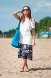 Mujer que recorre en la playa de la arena con el bolso Fotografía de archivo